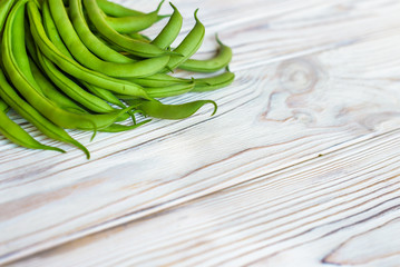 Bunch of freshly picked green beans on a wooden surface