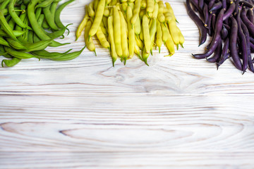 Collection of green, yellow and purple bush beans, opened green peas on wooden background