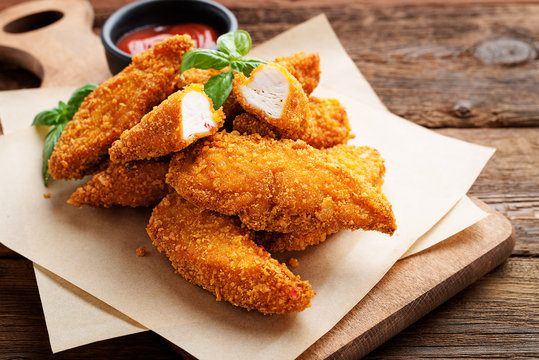 Delicious crispy fried breaded chicken breast strips with ketchup.