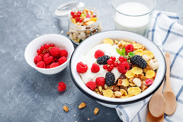 Healthy breakfast. Fresh granola, muesli with yogurt and berries on gray background. Top view. Copy space.