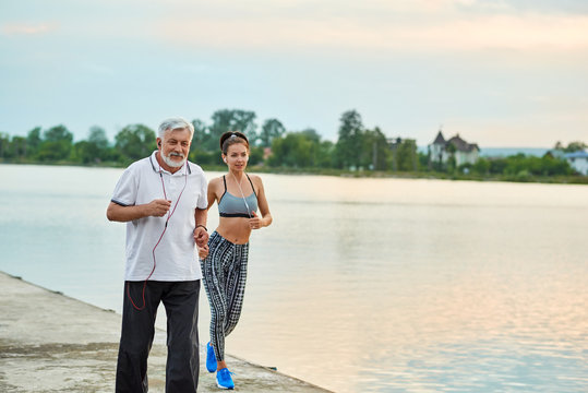 Senior man and active young girl running near city lake. Active lifestyle, healthy body. Sport, yoga, fitness. Different generations. Models having strong, fit figures. Modern sportswear.