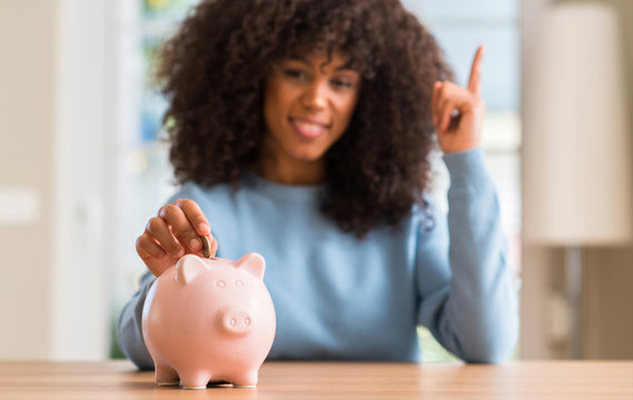 African american woman saves money in piggy bank surprised with an idea or question pointing finger with happy face, number one