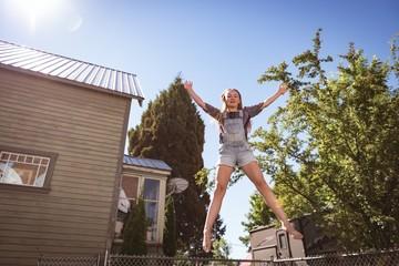 Girl jumping on trampoline in garden