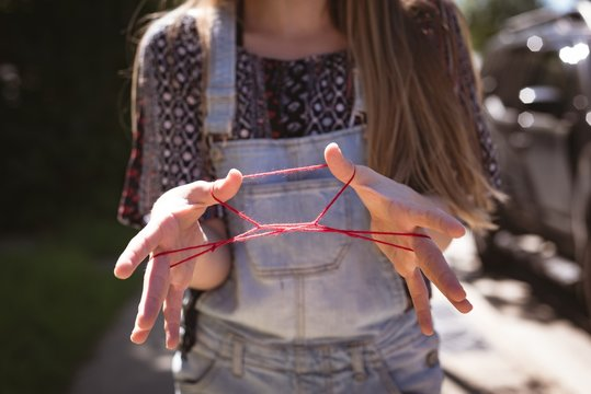 Girl playing string game with rubber band on a sunny day