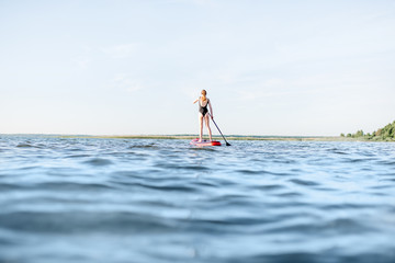 Beautiful young woman in black swimsuit paddleboarding on the lake with waves during the morning light