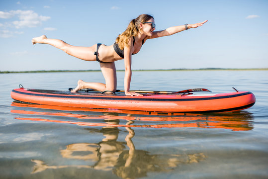 Young woman doing yoga on the paddleboard on the lake with calm water and reflection during the morning light