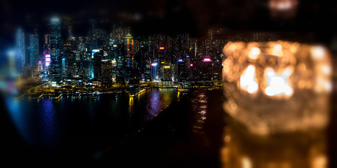 Fotomurales - Blured burning candle in glass cup with Hong Kong island night view background