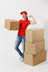 Full length portrait of strong delivery woman in red cap t-shirt showing biceps, muscles isolated on white background. Female courier standing near empty cardboard boxes. Receiving package. Copy space