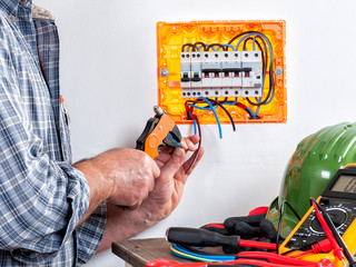 Electrician at work on cables with wire stripper.