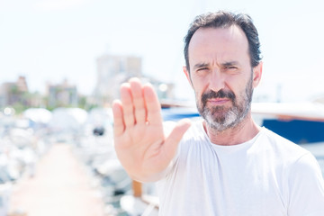 Handsome middle age man in marina with open hand doing stop sign with serious and confident expression, defense gesture