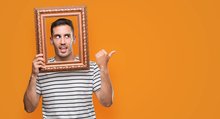 Handsome young man looking through vintage art frame pointing with hand and finger up with happy face smiling