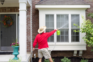Man spring cleaning the exterior of his house