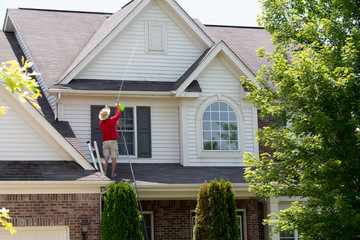 Man cleaning the upper floor exterior of his home