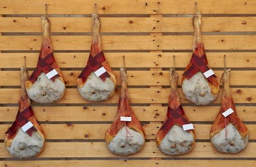 Leg hams of Prosciutto San Daniele, an excellent italian raw ham quality , hanging on a wooden wall