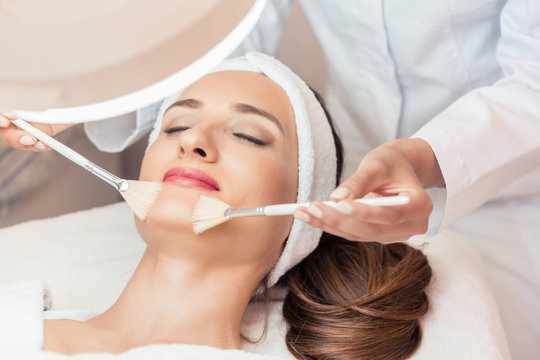 High-angle close-up view of the face of a beautiful woman during anti-aging facial massage with soft brushes in a modern cosmetic center