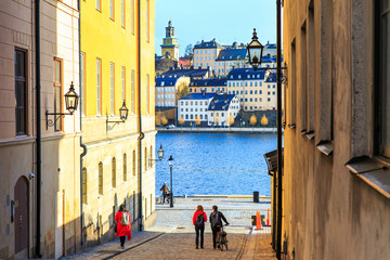 Tourists walking on cobble streets in Riddarholmen is part of Gamla stan is old town of Stockholm city, Sweden. Facades of medieval houses and exterior of historic buildings on shore of Baltic sea.