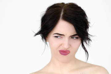 emotion face. discontent dissatisfied envious woman looking sideways and thinking. young beautiful brunette girl portrait on white background.