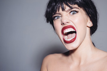 Enraged female in black wig screaming, madness concept. Young woman with furious face isolated on gray background