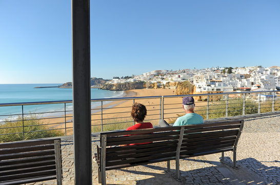Two elderly tourists sitting on a bench in the beach of Albufeira, one of the most visited by European tourism. Algarve, south of Portugal.
