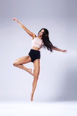 Beautiful young ballet dancer jumping on a light background.