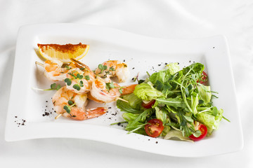 Tiger prawns on skewers with lemon and greens on a white dish
