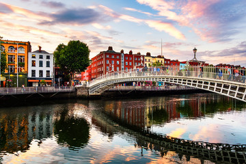 Zelfklevend Fotobehang Brug Night view of famous illuminated Ha Penny Bridge in Dublin, Ireland at sunset