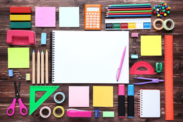 School supplies with blank sheet of paper on wooden table