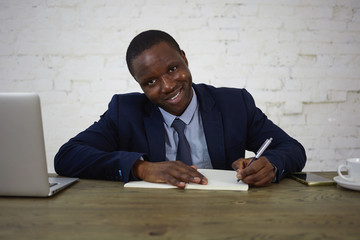 Picture of attractive African lawyer wearing suit working at his office desk, making notes in diary, looking and smiling at camera. Happy businessman writing down his ideas and plans in copybook
