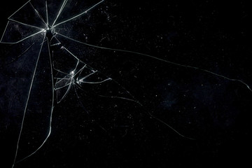 A broken glass on a black background, shattered pieces not too far away from each other. Useful texture for overlay.