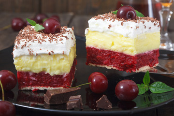 Homemade cherry cake with vanilla and whipping cream on wooden table. Decorated with cherries and mint leaves on top of cake pieces.