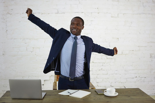 Handsome tired dark skinned businessman in elegant suit stretching arms, standing at desk with gadgets, notebook and mug of coffee, feeling relief after he finished work. People, job and occupation