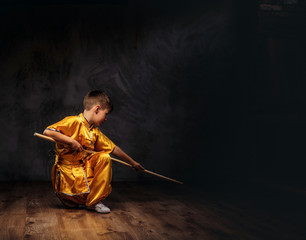 Cute boy dressed in the traditional costume of a Tibetan monk shows the tricks with dao stick from the wellness complex at a studio.