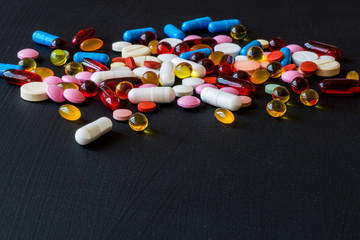 Different colorful medicines. Pills and capsules on black background. Copy space.