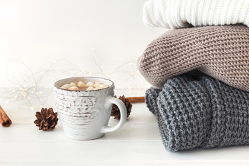Hot cocoa and pile of knitted sweaters.