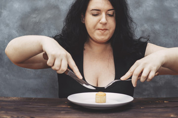 Gluttony, dieting, cheat meal, portion of sweets. Overweight  hungry woman pounce on food eating muffin