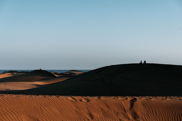 Couple sitting on top of Maspalomas Dunes on Gran Canaria during sunset