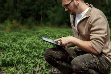 A male farmer sitting in the field and using a tablet. Modern application of technologies in agricultural activities. Farmland, new technologies, harvesting, fertilization, crop inspection.