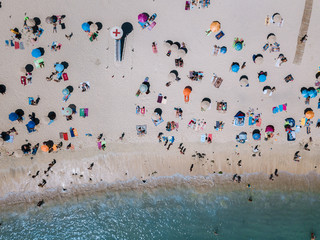 Aerial of People lying and playing on the beach during midday