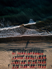 Red deck chairs on the beach during sunset with wavy ocean