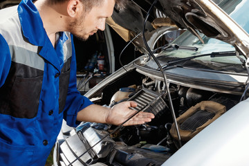 Male hands close-up, checks the oil level in the engine. The auto mechanic works in the garage. Repair service. Maintenance of the car, car repair.