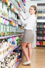 Girl customer shopping in modern perfumery, choosing perfume