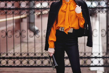 Street, office, bright style. Young woman, business style, black jacket, black pants, black handbag, sunglasses, orange blouse, belt, bracelet. Details. Wall mural
