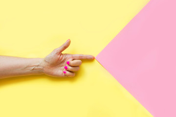 Female hand with pink nail on yellow. Concept.