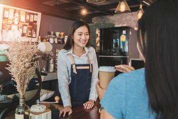 Young woman barista at cafe