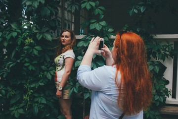 Woman taking photo of friend with smartphone