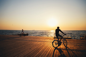 Couple of young hipsters cycling together at the beach at sunrise sky at wooden deck summer time