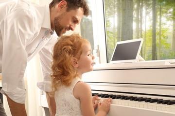 Papa Klavierlehrer Mädchen am Klavier