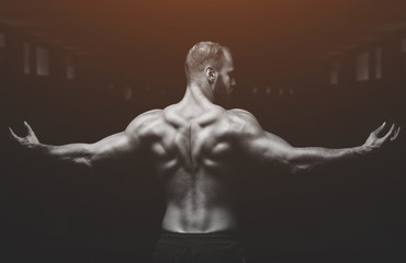 Silhouette of a slender bodybuilder doing sports in the gym.
