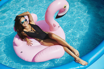 Fashionable, happy and smiling brunette model girl with perfect sexy body in stylish black bikini and glamorous sunglasses, posing on an inflatable pink flamingo at the swimming pool outdoors