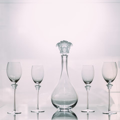 Set of empty glass decanter with four wine glasses